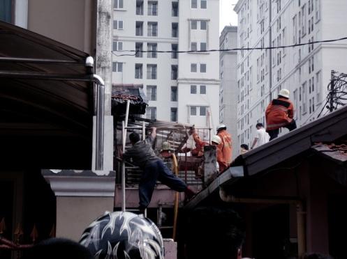 Petugas Pemadam dengan dibantu warga berusaha keras memadamkan api